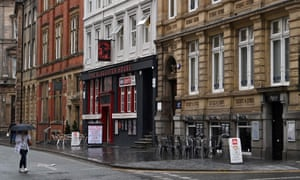 A pedestrian walks past the empty tables of pubs and restaurants in Liverpool