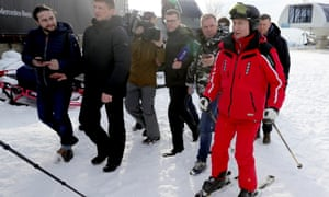 Vladimir Putin in skiing gear surrounded by reporters