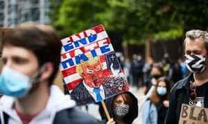 A protester holds a placard showing Donald Trump at a Black Lives Matter protest outside the US Embassy in London on 7 Jun 2020