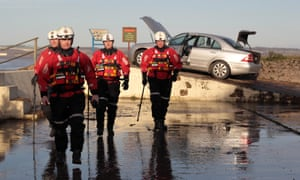 Humberside Fire and Rescue officers check a flood-damaged car in 2013.