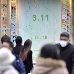 People read messages on the window of a store in the luxury shopping district of Ginza in Tokyo
