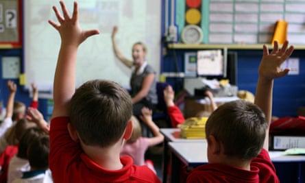 primary school children facing teacher in classroom hands raised