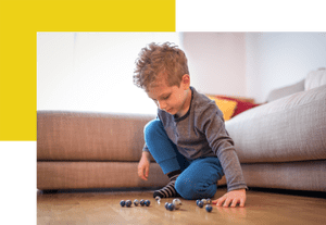 Young boy playing with marbles on living room floor