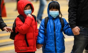 Children wearing face masks cross a road during a Lunar New Year of the Rat public holiday in Hong Kong on January 27.