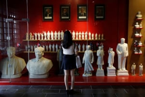 A visitor looks at a display of porcelain figures Chairman Mao