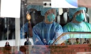 Medical workers and Diamond Princess passengers arrive at a Hong Kong quarantine centre