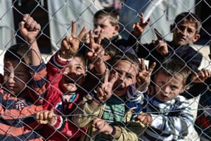 Young Syrian Kurdish boys make the 'V for victory' sign behind a fence at a refugee camp