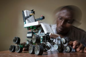 Peter Mbiria is seen with a scale model prototype for his all-terrain electric convertible wheelchair
