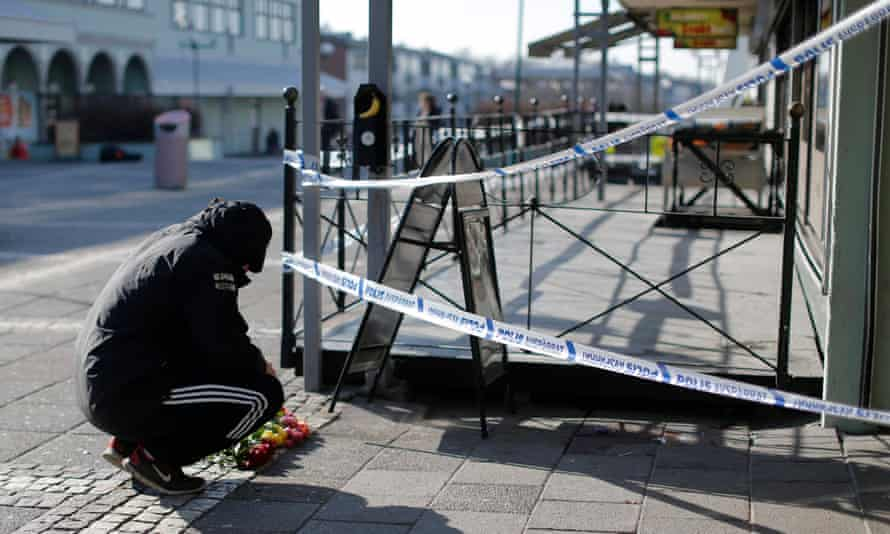 A man lays flowers at the scene of a fatal shooting in Gothenburg, Sweden, in March 2015.