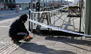 A man lays flowers outside a pub in Gothenburg which was the scene of a suspected gang-related shooting