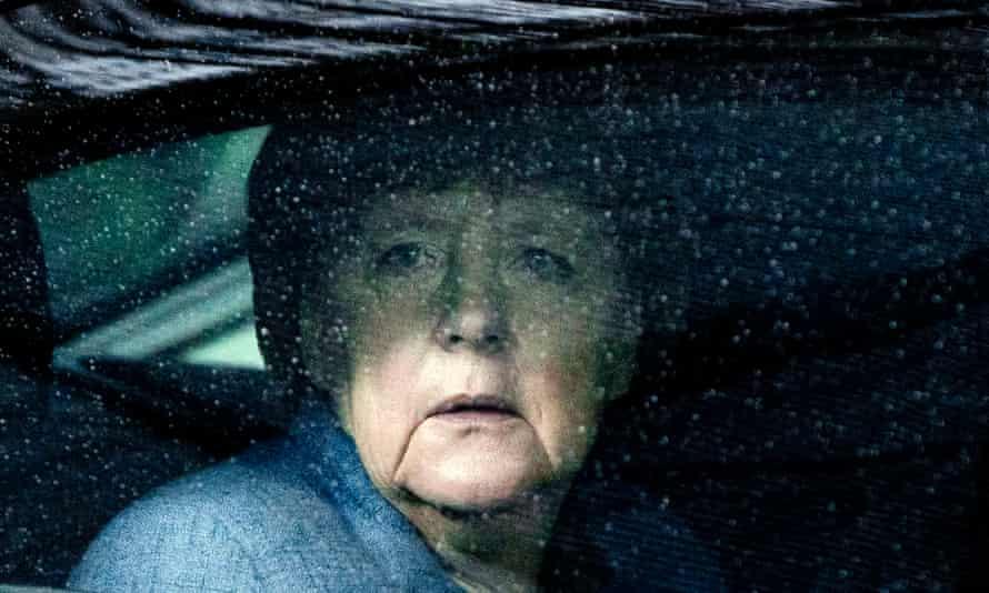 Angela Merkel arrives in the rain to meet east European leaders in Brussels on Friday.