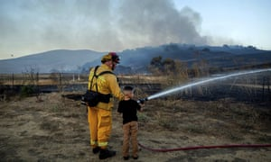 Capt Eli Cronbach, a firefighter with the city of Napa, lets Dylan Ramirez, six, spray water as crews work to contain the American Fire in American Canyon, California, early this month.