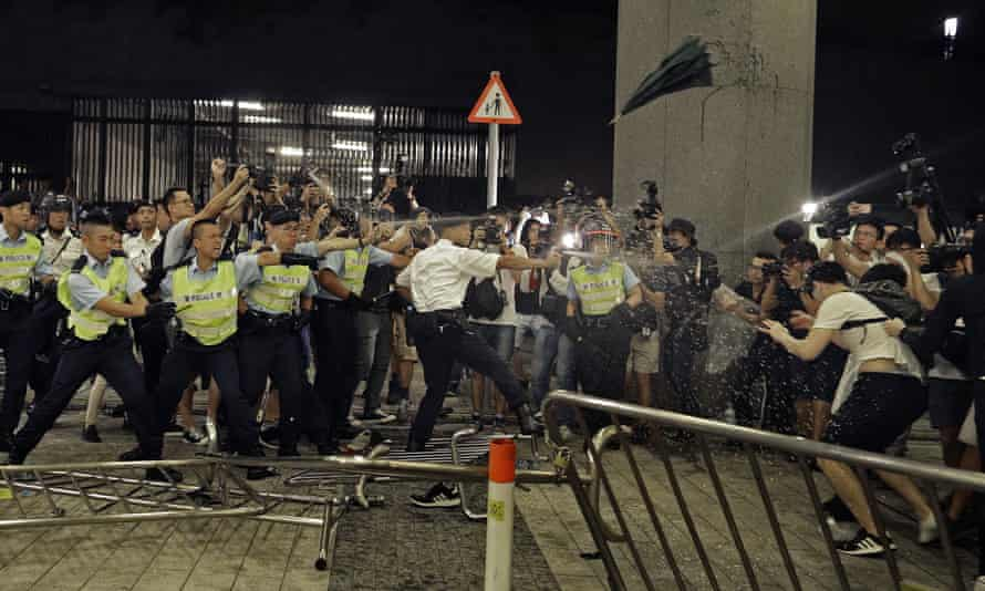 Police officers use pepper spray against protesters in Hong Kong.