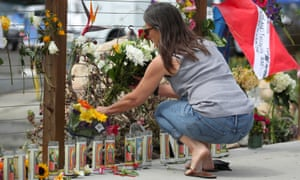 A woman places flowers at a makeshift memorial near Truth Aquatics in Santa Barbara, California.
