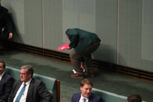 A parliamentary attendant picks up papers thrown by a protester from the public galleries during question time