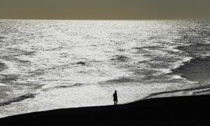 A lone figure enjoys a stroll in the sunshine on Brighton beach