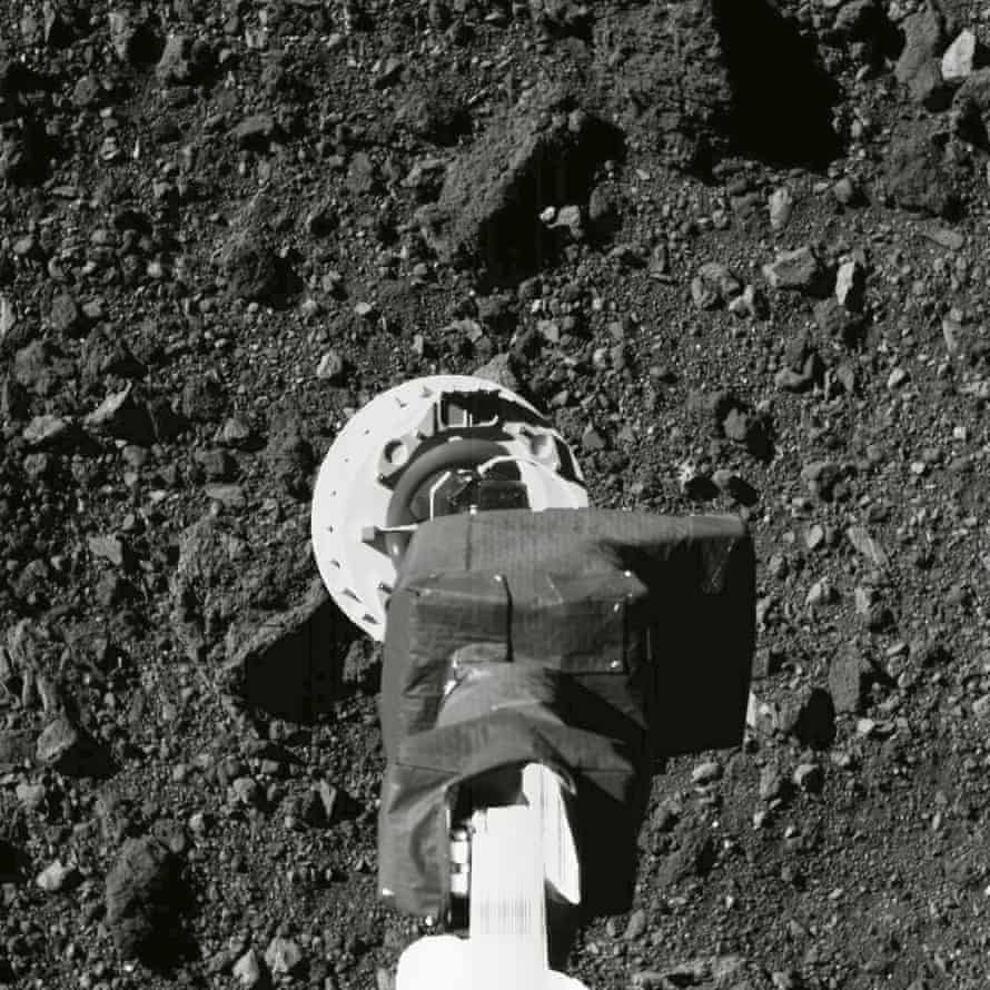 The sampling arm of the Osiris-Rex spacecraft is tested during a rehearsal landing on the surface of the asteroid Bennu.