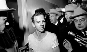 In this 23 November 1963 picture, Lee Harvey Oswald, surrounded by detectives, talks to the media as he is led down a corridor of the Dallas police station for another round of questioning.