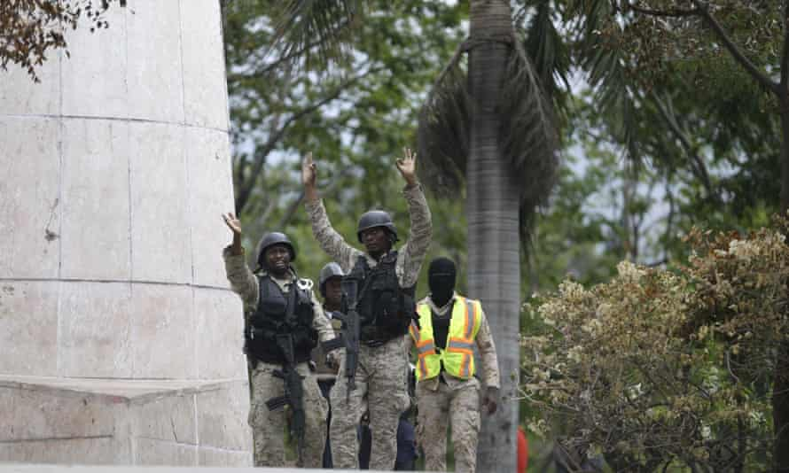 OfficersPolice officers gesture for all sides to cease fire during a clash with army soldiers as they protested over police pay and working conditions, in Port-au-Prince, Haiti, Sunday, Feb. 23, 2020. Off-duty police officers and their supporters exchanged fire for nearly two hours with members of the newly reconstituted Haitian army in front of the national palace. (AP Photo/Dieu Nalio Chery)