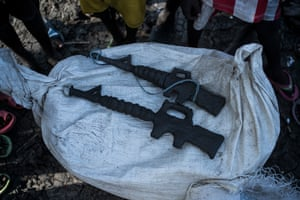 M16 rifles, sculpted in mud by children, are seen in Aboko