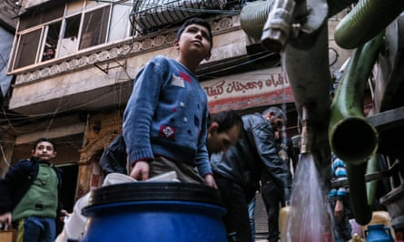 Boys fill containers with drinking water from a tank in Salah al-Din, Aleppo.