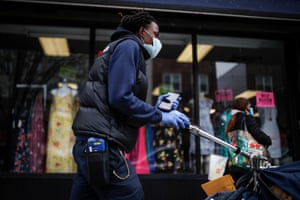 A postal worker wears a protective mask and gloves while operating a route in the Queens borough of New York.