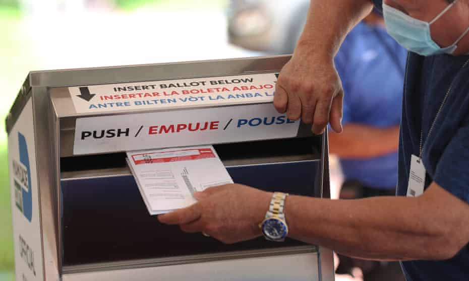 A poll worker places mail ballots into a box at the Miami-Dade Election Department on 14 October.