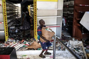 A young boy reacts as he collects food and drinks from a burnt down and looted Auchan supermarket in the up-market area of Almadies as protests have been ongoing for three days after opposition leader Ousmane Sonko was arrested following rape charges