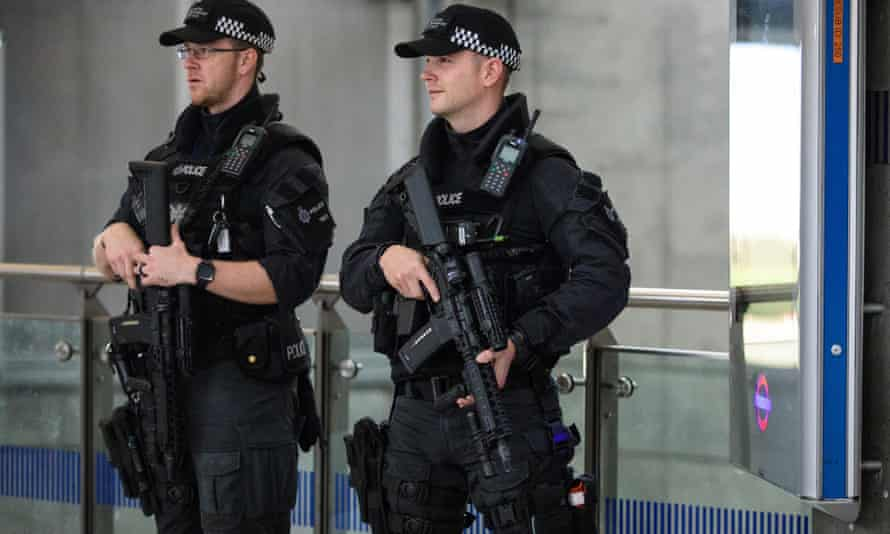 Armed police patrol Westminster tube station after a terrorist attack.