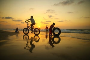 Children play on the beach at sunset near Gaza City in the Palestinian territories