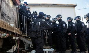 Israeli police in riot gear enter a prefabricated house during the eviction of the illegal settlement outpost of Amona.