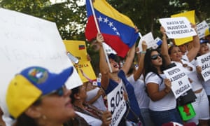 Venezuelan residents in Panama yell slogans and hold signs during a protest against Venezuela's president Nicolas Maduro.
