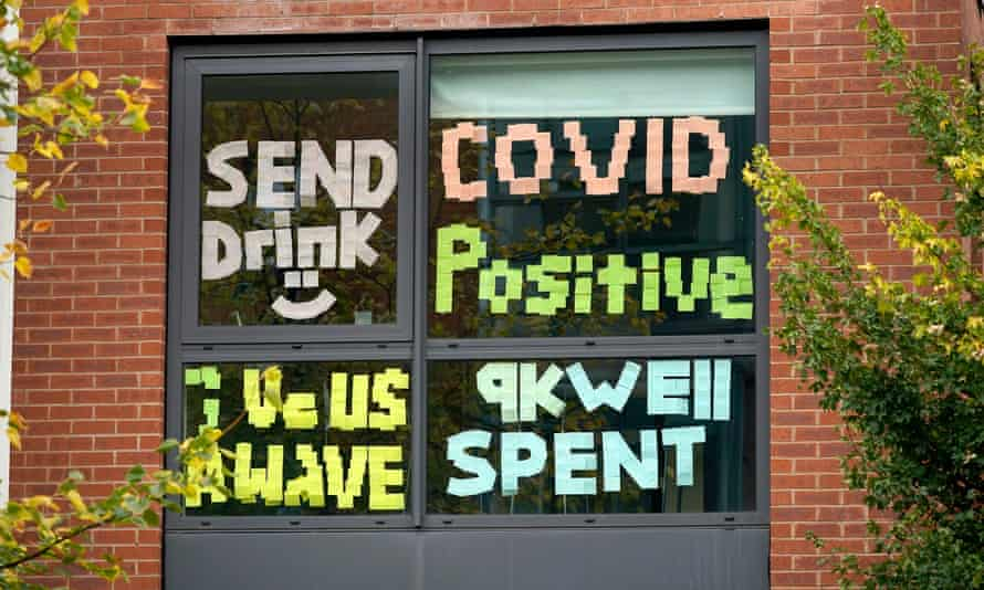 "Signs made by locked-down students in Manchester, reading ""send drink"", ""Covid positive"", ""Give us a wave"" and ""9k well spent"""