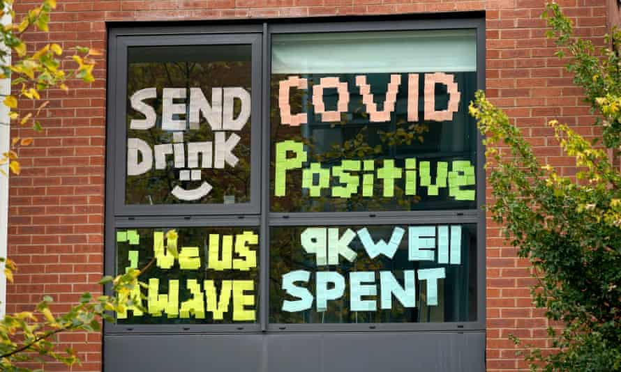 Signs made by students in a locked-down accommodation building in Manchester, reading 'Send drink', 'Covid positive', 'give us a wave' and '9k well spent'