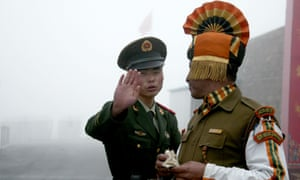 A Chinese soldier gestures to an Indian soldier at the disputed Bhutan border.