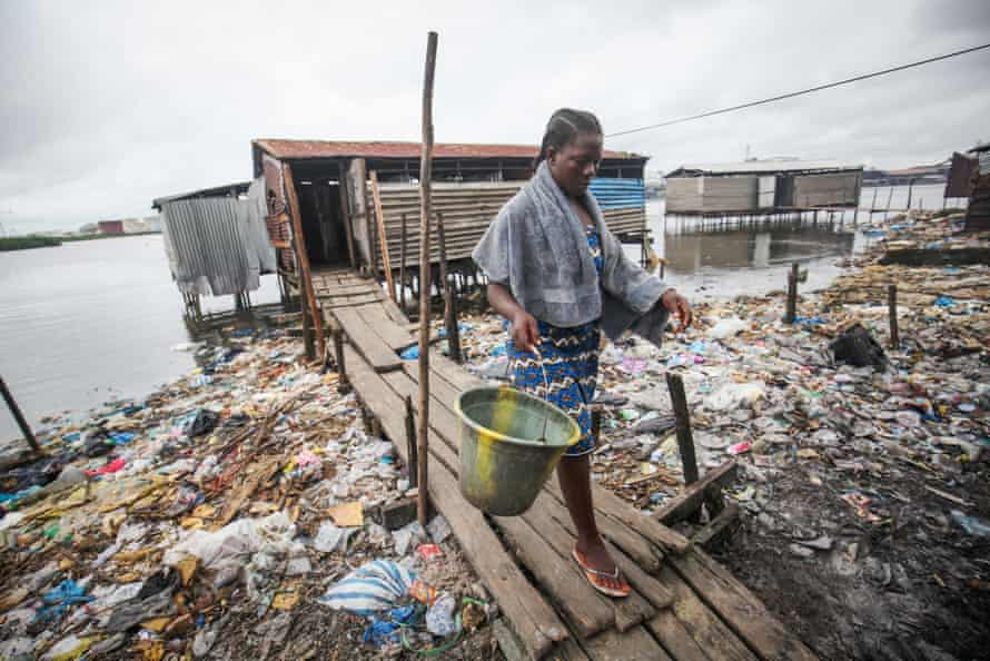 Roselyn Kwesi on her way home after using a bathing and toilet facility that empties straight into the water in Fanti Town, Monrovia, Liberia.