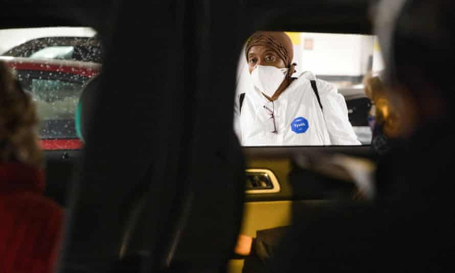 A nurse consults with people waiting in their vehicles to receive Covid vaccines in Detroit, Michigan, on 15 January.
