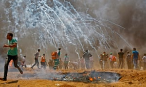 Palestinians run for cover from tear gas during clashes with Israeli security forces east of Jabalia.