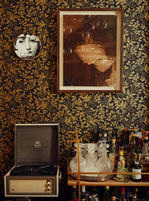 A Fornasetti plate and a painting by Julia Hamilton above a turntable and drinks trolley.
