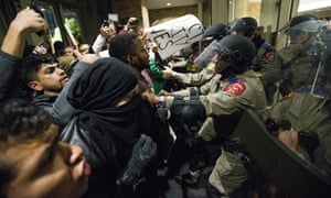 Law enforcement officers push protesters out of the Texas A&M University student center where Richard Spencer, who leads a white nationalist organization, was speaking on Tuesday.