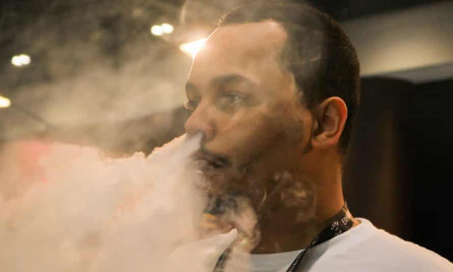 A man exhales after vaping at the Vape Jam Convention in London in April 2018.