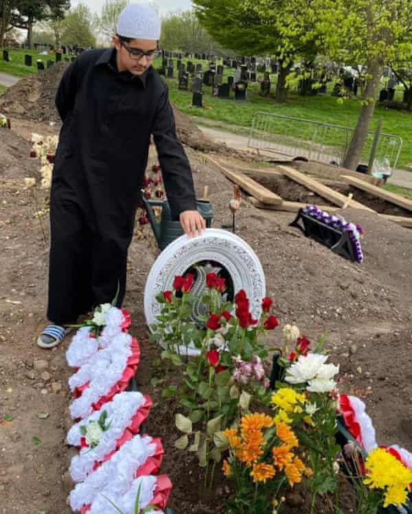 A mourner attends Choudhary Aslam Wassan's grave.