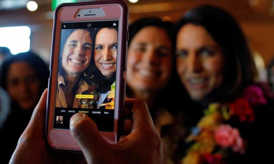 Gabbard poses for a photograph with a diner at the Green Elephant in Portsmouth, New Hampshire, 17 February 2019.