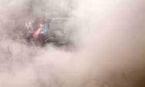 A Bangladeshi rickshaw puller rides past smoke created by burning waste materials on a street in Dhaka.