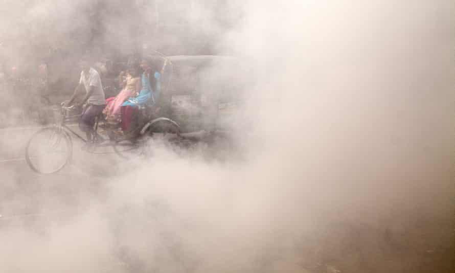 A Bangladeshi rickshaw puller rides past smoke created by burning waste materials on a street in Dhaka.