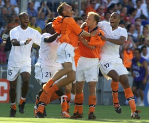 Holland's Dennis Bergkamp, who scored the winning goal against Argentina, is mobbed by cheering teammates at the end of the quarter final.