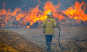 A firefighter battles a blaze in Yanchep, north of Perth, Western Australia, where bushfires were on Sunday threatening lives and homes.