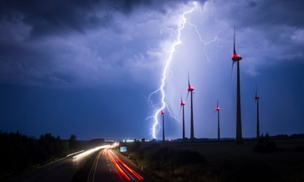 Lightning strikes behind wind turbines during a thunderstorm near the border between Germany and Poland.