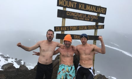 Carney with Wim Hof and a fellow disciple, all bare-chested, linking arm and with fists of defiance, near the summit of Kilimanjaro.