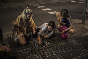 A girl draws a peace symbol on the street as a tribute to the victims of the Barcelona terrorist attack